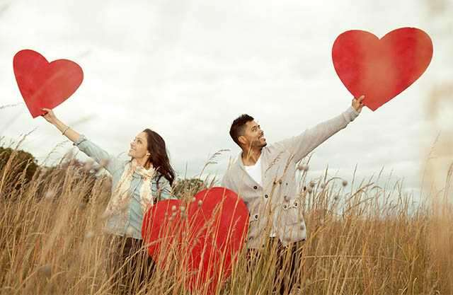 couple holding heart sign