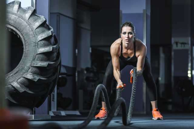 woman battle ropes workout