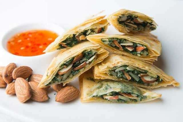 Baked spinach and almond parcels Serves: 4 Prep time: 20 minutes Cooking time: 15 minutes Ingredients 400 g cooked chopped spinach  100 g almond flakes, chopped 200 g mascarpone cheese 15 g salt 10 g pepper  12 spring roll pastry sheets 200 ml oil 20 g red chilli powder Method Squeeze out all the water from the cooked spinach and mix with chopped almond flakes, mascarpone cheese and seasoning.  Oil the spring roll sheets and sprinkle red chilli powder. Fold four times and then repeat the layering. Cut the layered sheets into half triangles and fill with the spinach mixture. Close the triangle parcels using a slurry made with maida and water. Brush the parcels with butter or oil and bake in a preheated oven at 180°C for 8 to 10 minutes. Serve hot. Recipe: Chef Ajay Chopra