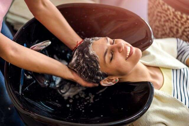 woman washin hair with a sulphate-free, paraben-free shampoo