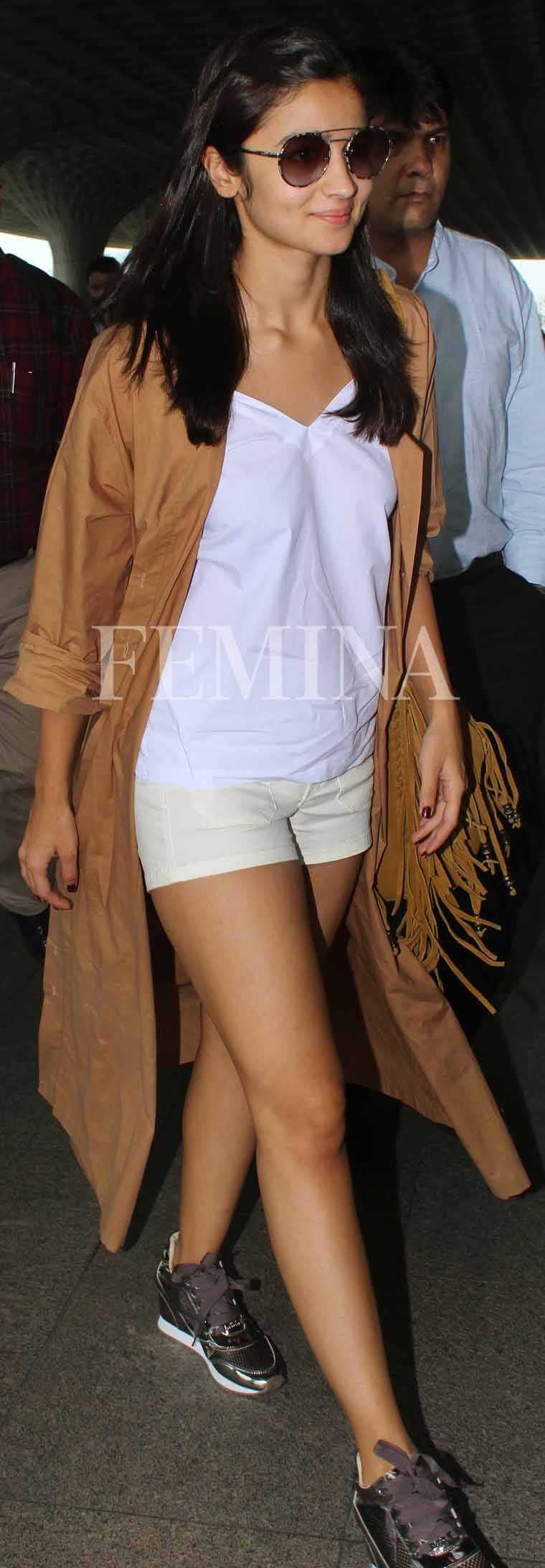 Alia Bhatt nails travel style in a long camel coat layered over hot pants and a tee.