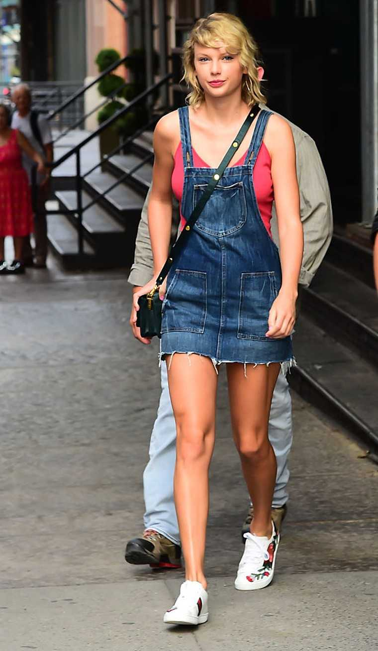 Taylor Swift showed off her toned gams in a denim dungaree dress and Gucci kicks.