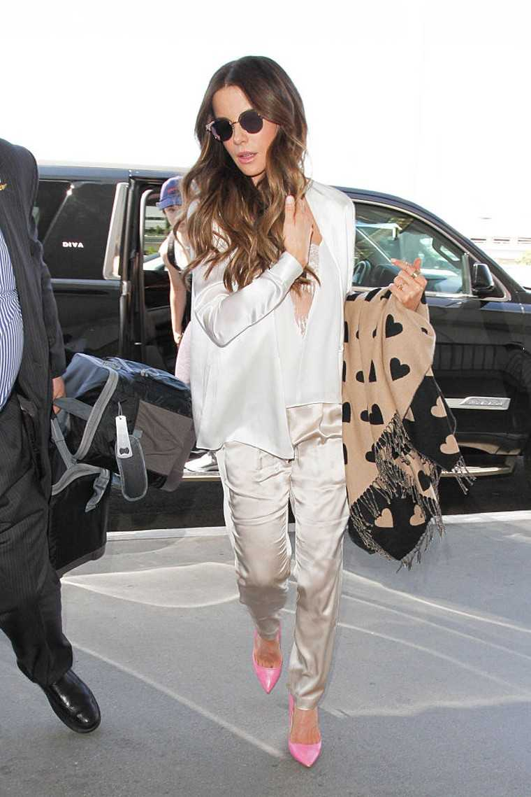 Kate Beckinsale nailed travel style in a luxe satin shirt and matching pyjamas paired with hot pink Rupert Sanderson heels.