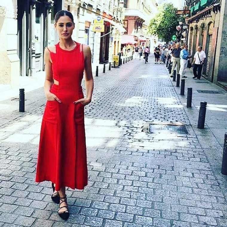 NARGIS FAKHRI While travelling, Nargis opted for a red-hot Fendi midi dress with cut-aways. Any dress that has pockets gets full marks from us.