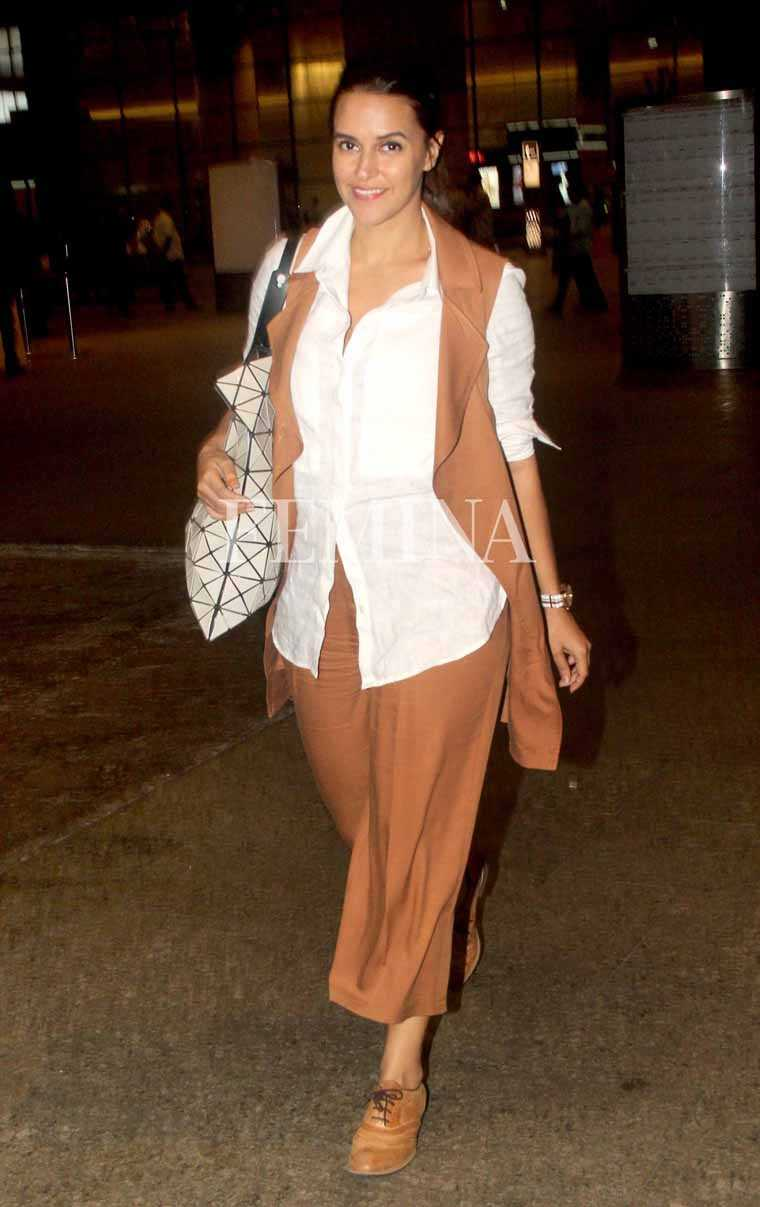 Neha Dhupia wears her Marks & Spencer culottes and sleeveless jacket set with a white shirt and classic tan brogues.