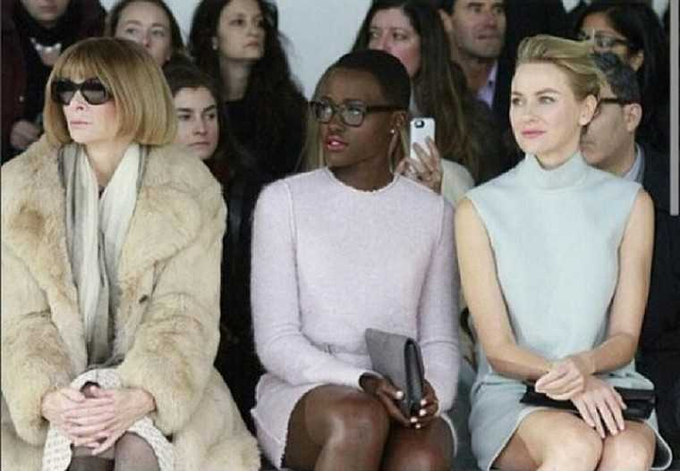 LUPITA NYONG'O This fresh-faced actor from the film 12 Years a Slave is fashion's new darling and here she takes her glasses to the front row of a fashion show and right next to Anna Wintour. A red lip and a soft pink dress keep her look FROW worthy.