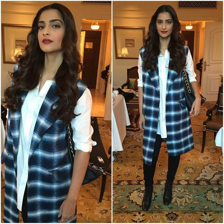 Sonam Kapoor layered her white shirt with a Dhruv Kapoor long line jacket for a recent event.  She completed her look by adding a pair of ankle length boots.