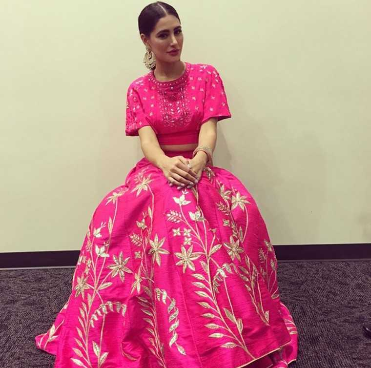 Nargis Fakhri nails festive dressing in her embellished crop-top-and-lehenga-combo by Anita Dongre. She keeps the accessories to the bare minimum with just a pair of statement chaandbali earrings.