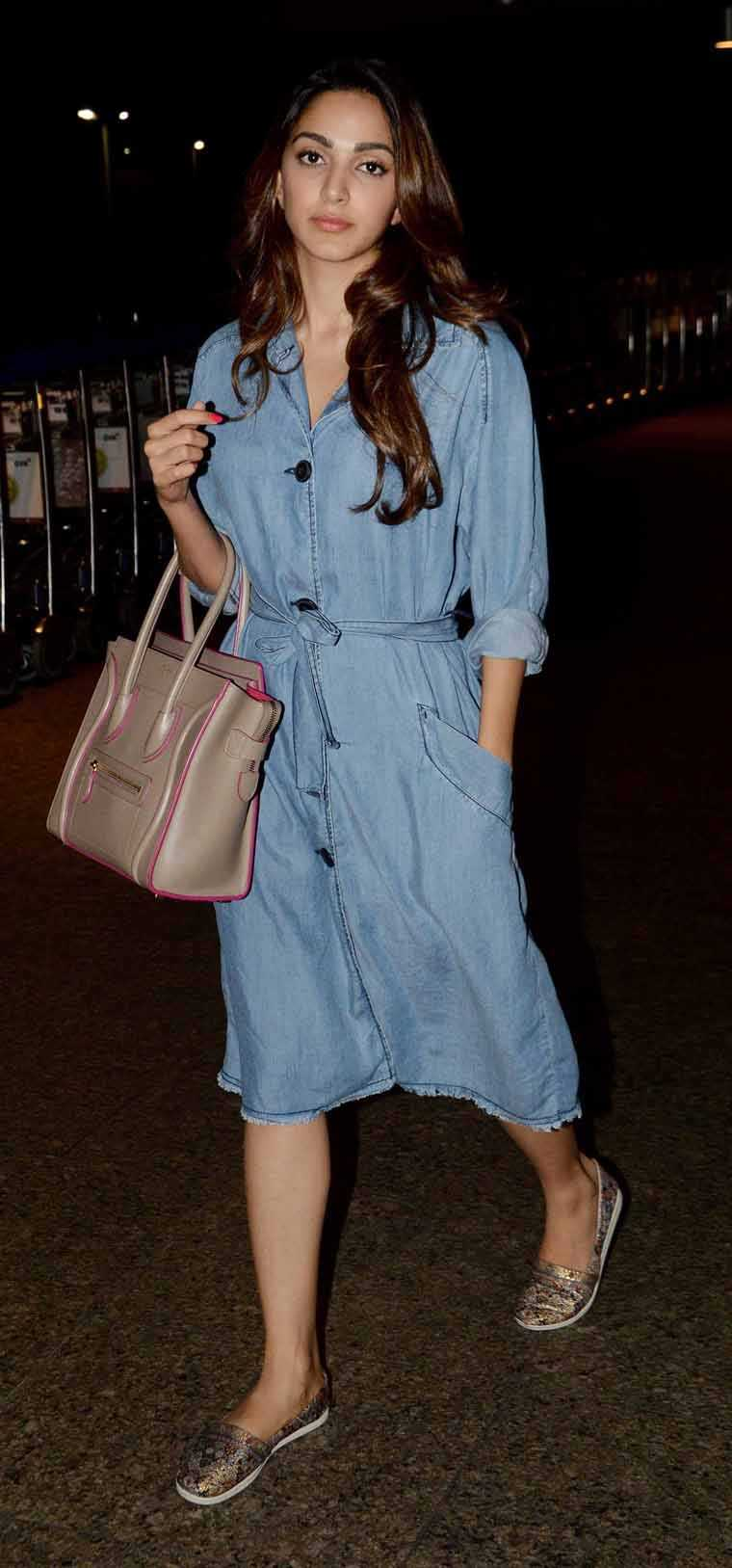 MS Dhoni star Kiara Advani nailed travel style in a chic denim dress, a beige tote bag and a pair of sparkly slip-ons.