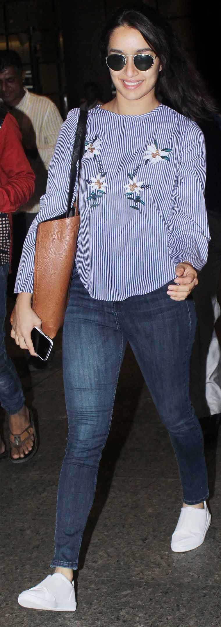 Shraddha Kapoor aced travel fashion in a breezy striped blouse paired with denims and white kicks.