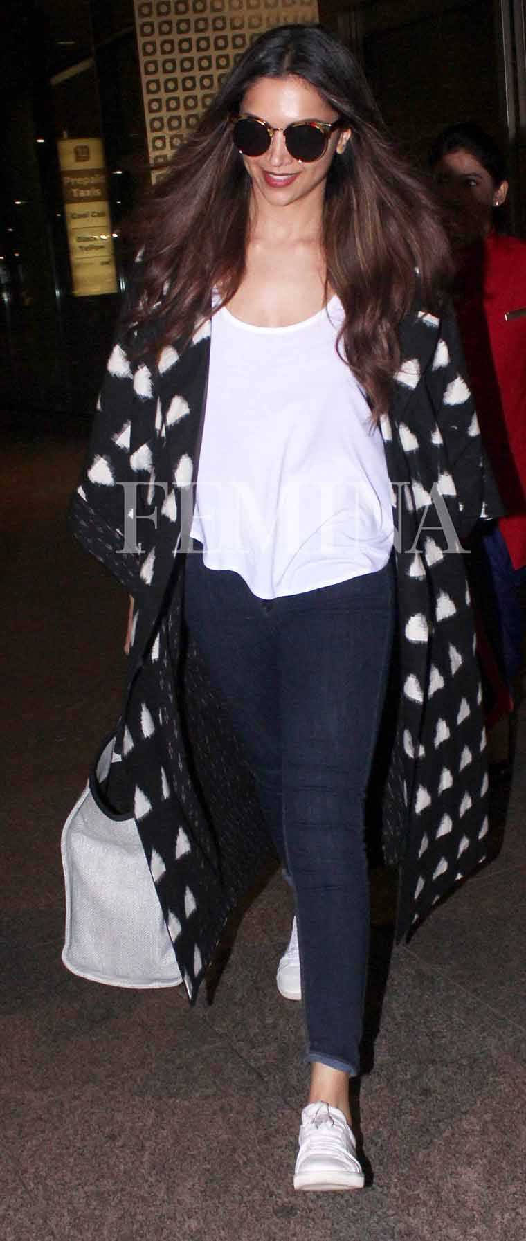 A long monochrome jacket from Chola elevated Deepika Padukone's travel uniform comprising skinny jeans, a tee and white sneakers. Her trusty Chanel tote and a pair of cat-eye sunglasses keep her company.
