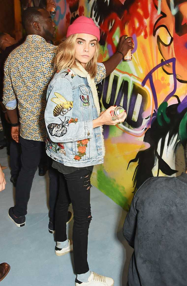 Model and Suicide Squad star Cara Delevingne steps up her street-style game in a Gucci jacket, ripped denims and a beanie.